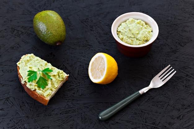 Guacamole sandwich. citroen, avocado op een zwarte achtergrond