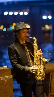 Guangzhou, china - 15 maart 2016: man saxofoon spelen op straat in de avond