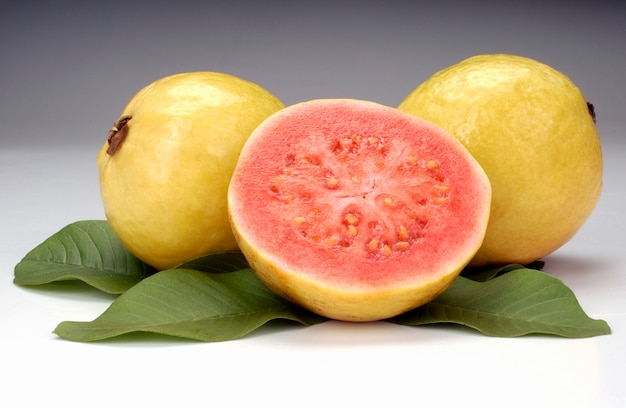 Guaves in tweeën gedeeld en bladeren op witte achtergrond tropisch fruit