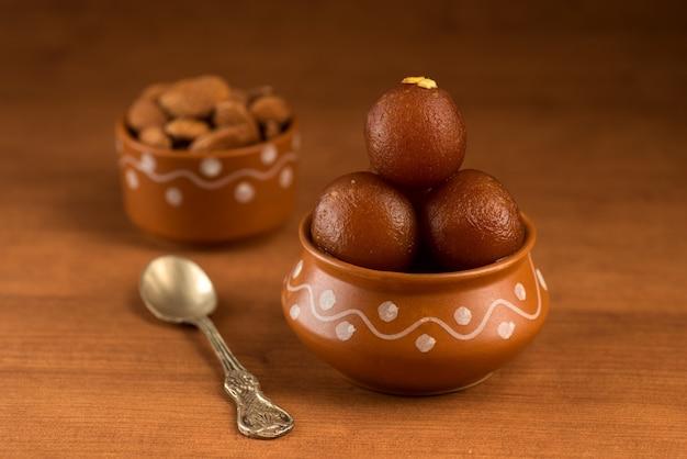 Gulab jamun in aarden pot met lepel en droog fruit. indiase dessert of zoete schotel