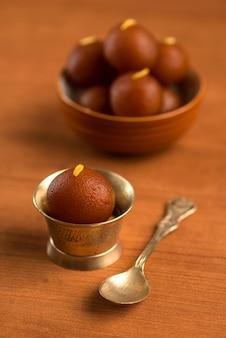 Gulab jamun in kom en koperen antieke kom met lepel. indiase dessert of zoete schotel.