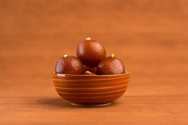 Gulab jamun in kom op houten achtergrond. indiase dessert of zoete schotel.