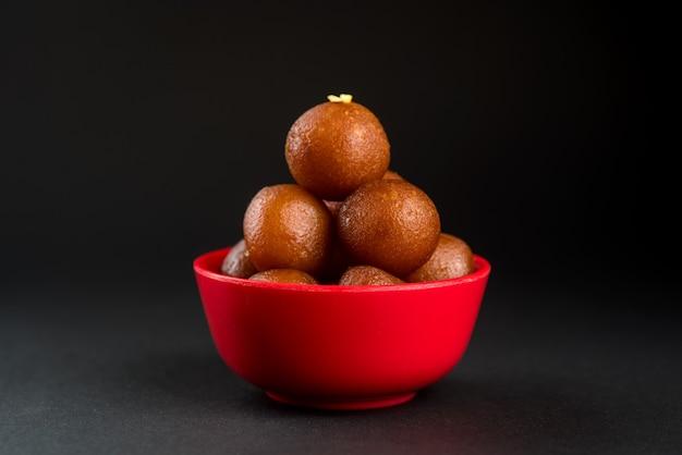 Gulab jamun in kom op zwarte achtergrond. indiase dessert of zoete schotel.