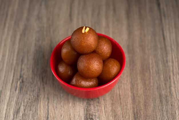 Gulab jamun in rode kom op houten achtergrond. indiase dessert of zoete schotel.