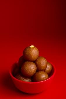 Gulab jamun in rode kom op rode achtergrond. indiase dessert of zoete schotel.