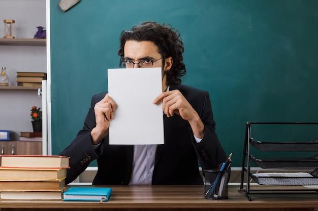 Gulzige mannelijke leraar met een bril die vasthoudt en een bedekt gezicht met papier aan tafel zit met schoolhulpmiddelen in de klas