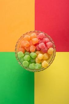 Gummy candy, arrangement van gummy candy van bovenaf gezien in een glazen pot op een gekleurd oppervlak.