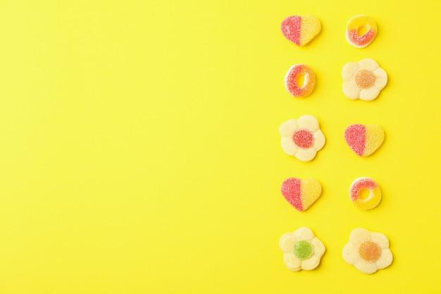 Gummy snoepjes op gele achtergrond, ruimte voor tekst.