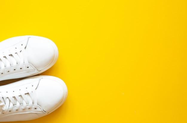Gumshoes wit op een gele tafel met bovenaanzicht.