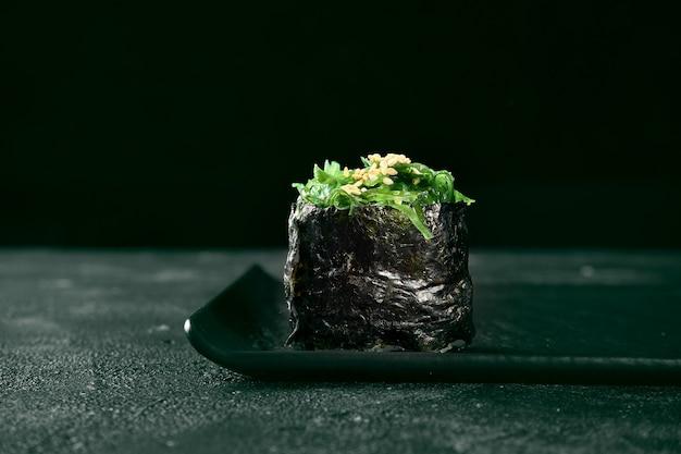 Gunkan maki sushi met hiyashi zeewier op een zwart bord met gember en wasabi. japanse keuken. voedsellevering. zwarte achtergrond
