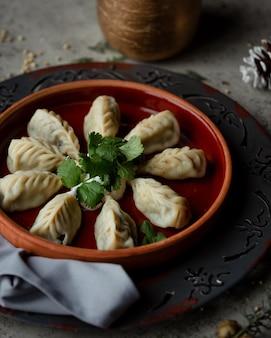 Gurza azerbaijani dumplings geserveerd met yoghurt in aardewerkverbod