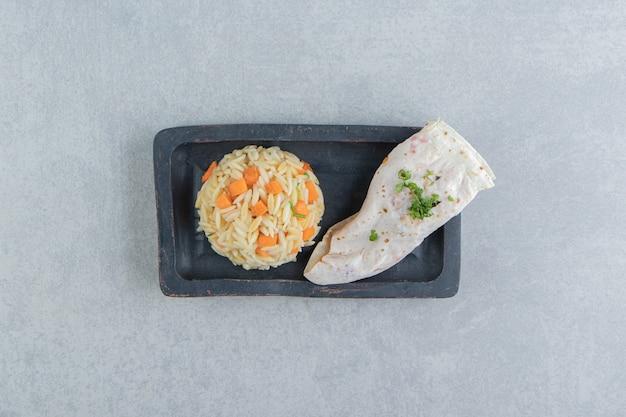Gutabs naast rijst op het bord, op het marmer.