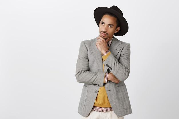 Guy concentreerde zich op zijn gedachten en nam een moeilijke beslissing. geconcentreerde serieuze donkere mannelijke freelancer in zwarte hoed en stijlvolle jas, kin aanraken, opzoeken met bezorgde doordachte uitdrukking