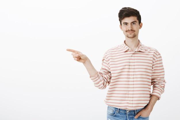 Guy geeft zijn collega de schuld. tevreden zelfverzekerde jonge blanke man met gestreept overhemd, naar links wijzend met wijsvinger en grijnzend, zelfverzekerd