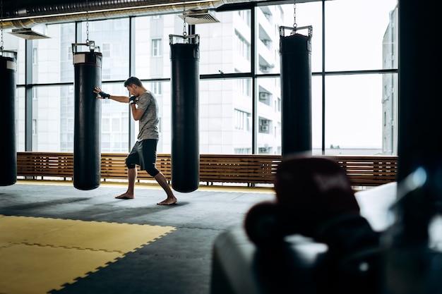 Guy gekleed in het grijze t-shirt en zwarte korte broek staat op wacht en werkt een boksstoot uit naast een hangende bokszak tegen de achtergrond van panoramische ramen in de sportschool.