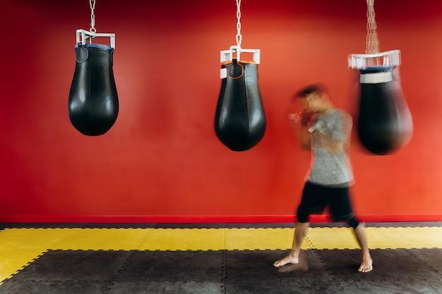 Guy gekleed in het grijze t-shirt en zwarte korte broek werkt met een zwarte bokszak tegen een rode muur in de sportschool.