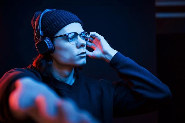 Guy geniet van de muziek. studio opname in donkere studio met neonlicht. portret van ernstige man