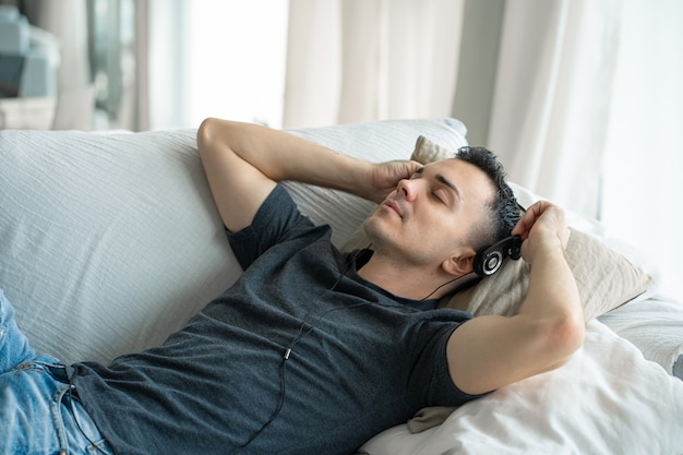 Guy geniet van de muziek terwijl hij op de bank ligt met een koptelefoon