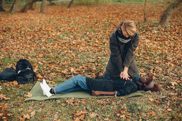 Guy helpt een vrouw. afrikaans meisje ligt bewusteloos. eerste hulp verlenen in het park.