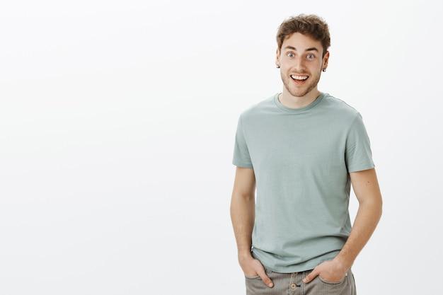 Guy hoort geweldig nieuws, voelt zich gelukkig voor vriend. portret van positieve vriendelijk ogende knappe man in t-shirt