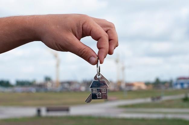 Guy houdt de sleutels van het huis in zijn handen