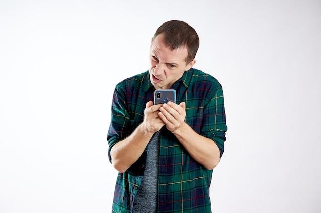 Guy houdt de telefoon in zijn handen en wijst ernaar met zijn vinger. een man speelt op zijn telefoon en kijkt naar video's, sociale netwerken