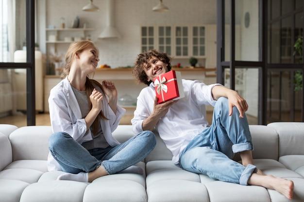 Guy houdt een cadeautje voor zijn verbaasde vriendin op de bank in de woonkamer. om geschenken te geven.