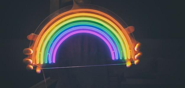 Guy houdt 's nachts neon led regenboog in handen