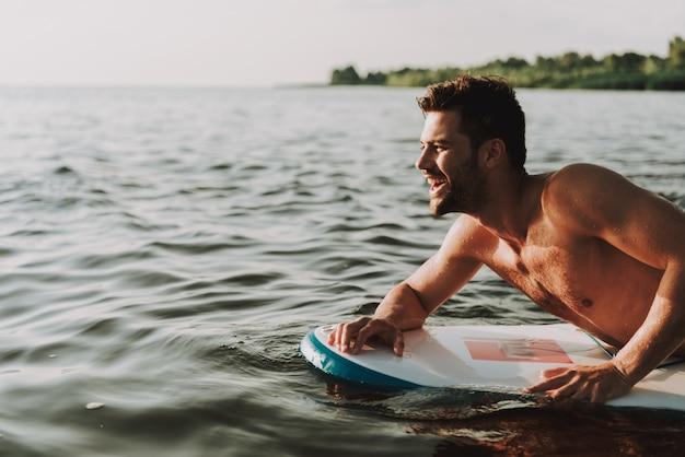 Guy is lays on surf in het water en zwemt.