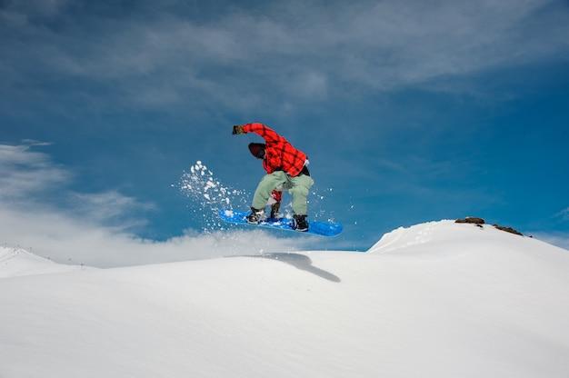 Guy is springen op een blauwe snowboard van een besneeuwde berg