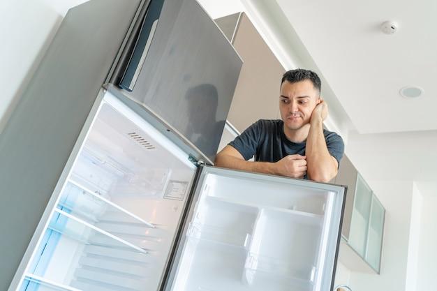 Guy is verdrietig bij de lege koelkast