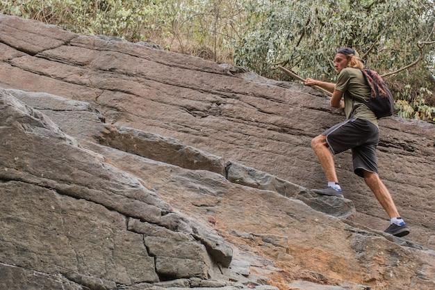 Guy klimt op de rotsen