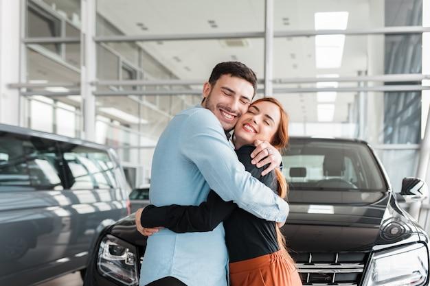 Guy knuffelt zijn vriendin in een autodealer
