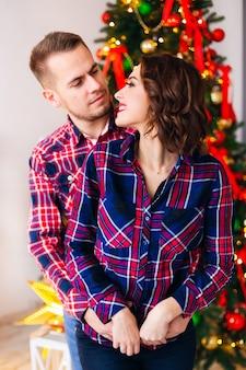 Guy knuffelt zijn vriendin van achteren en ze kijken elkaar aan tegen de ruimte van de kerstboom