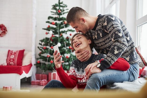 Guy kust zijn meisje in het hoofd terwijl ze smartphone vasthoudt. gelukkige jonge mensen zitten op de vensterbank in de kamer met kerstversiering.