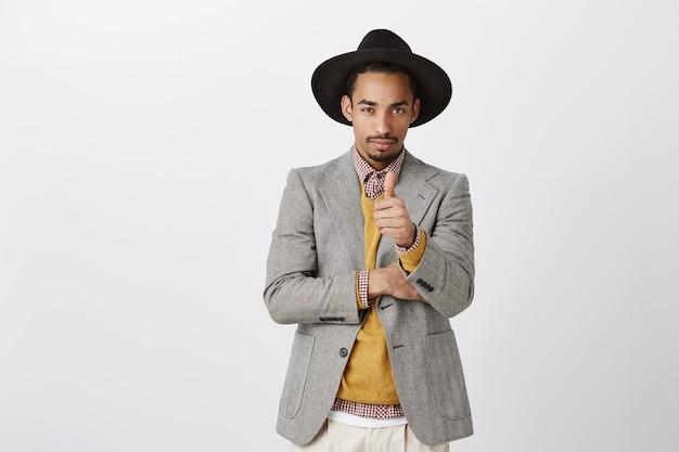 Guy kwam om zaken te doen. portret van ernstige knappe afrikaanse ondernemer in stijlvolle zwarte hoed en jas, duim opdagen, wordt gefocust tijdens de bespreking van nieuw concept van werk op kantoor