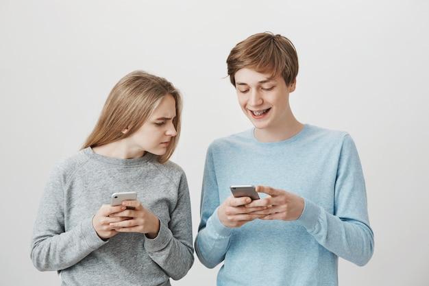 Guy lachend als op zoek grappige video en meisje gluren zijn telefoonscherm