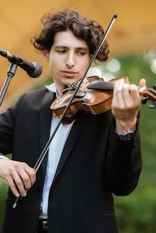 Guy-muzikant speelt de trommel tijdens een concert in podiumverlichting