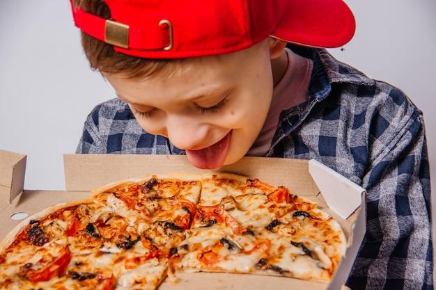 Guy opent met veel enthousiasme en ongeduld een doos pizza op een witte achtergrond