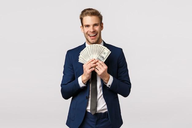 Guy opscheppen met geld. aantrekkelijke blonde bebaarde zakenman in klassiek pak, houden veel contant geld, tonen dollars en glimlachen tevreden, won loterij, sportweddenschap, tevreden witte achtergrond