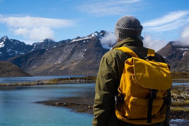 Guy reist met een gele rugzak door pittoreske plaatsen met prachtige berglandschappen.