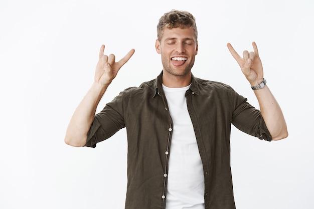 Guy rockt, voelt zich cool en geweldig met rock-n-roll-gebaar sluit de ogen en steekt de tong opgewonden en zorgeloos een gelukkig gevoel opheft van geweldige vibes na een concert over een grijze muur