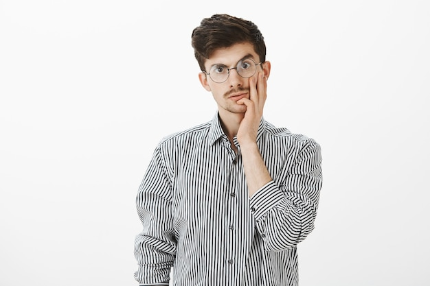 Guy schrok hoe stom zijn collega is. portret van verbijsterd kaukasisch mannelijk model met snor, wang aanraken en staren met clueless uitdrukking, geschokt door domme persoon