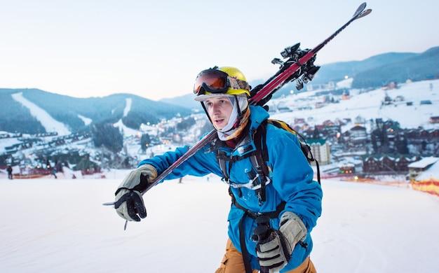 Guy skiër met stokken op zijn schouder en staren in de verte tegen de achtergrond van het skigebied