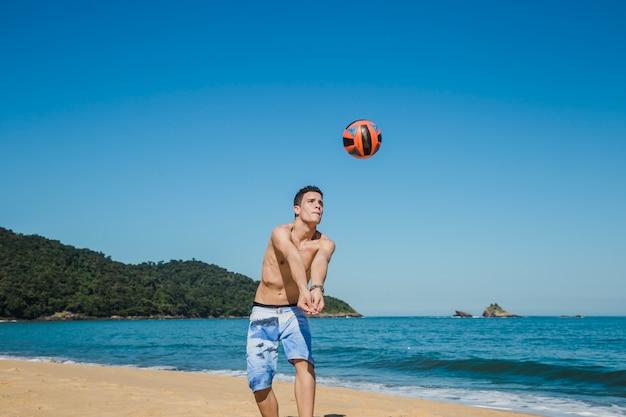 Guy slaat volleybal op het strand