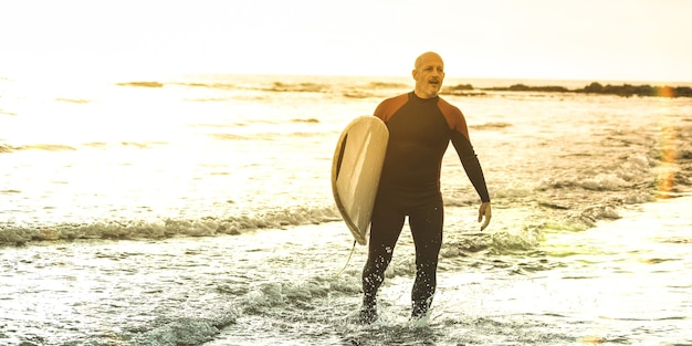 Guy surfer wandelen met surfplank bij zonsondergang in tenerife - surf longboard training beoefenaar in actie - sportreisconcept met zachte focus door achtergrondverlichting - warme zonneschijn kleurgefilterde tonen