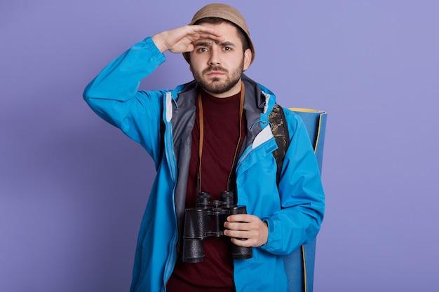 Guy toeristische wandelaar met rugzak en reismat, jas en hoed dragen, staat met verrekijker over zijn nek
