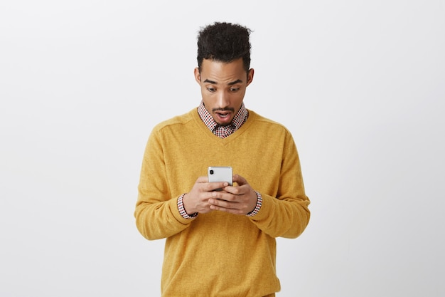 Guy typte zijn symptomen op internet, geschokt. portret van opgewonden, verbaasde, donkere man met afro-kapsel, kaak laten vallen en naar adem happen, spraak verliezen tijdens het lezen van bericht op smartphone