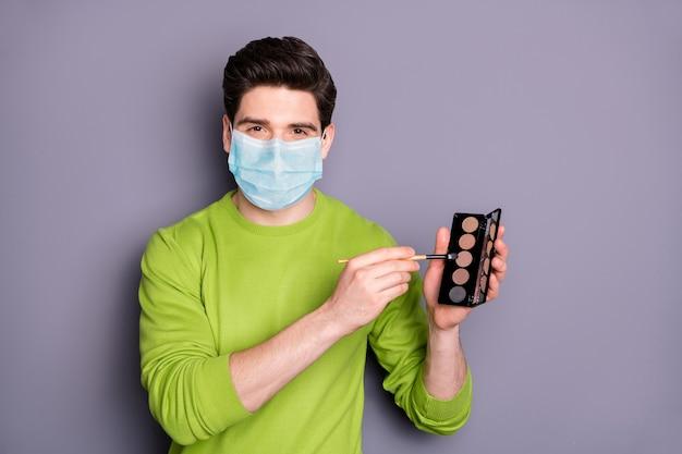 Guy visagist draag veiligheidsmasker, houd oogschaduwpalet vast en maatregelen ter preventie van griep