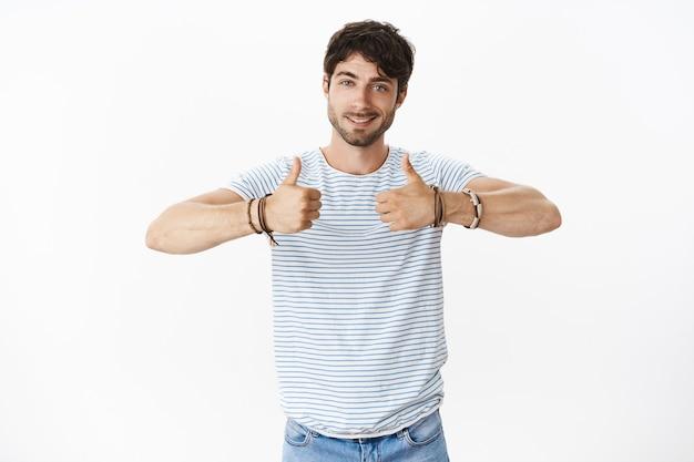 Guy vrolijkt vriend op, geeft positieve feedback en verzekert dat het spelen geweldig was met duimen omhoog en vriendelijk glimlachend, vriendelijk aan de voorkant ondersteunend en optimistisch poserend tevreden over grijze muur
